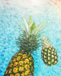 Op de 10 vrolijkste Instagramaccounts van zeer geliefde Instagrammers in dit artikel kom je veel foto's tegen zoals deze: twee ananassen die drijven in een zwembad met turquoise water.