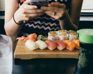 Sushifans maken foto's van hun sushi, zoals deze vrouw.