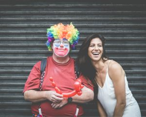 Man, die verkleed is als een clown, en een vrouw staan beiden awkward op de foto.