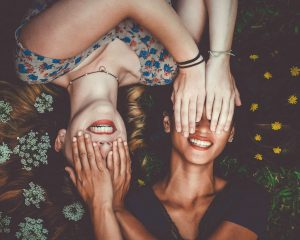 Twee meisjes liggen tussen de bloemen, leggen elkaars handen op elkaars ogen en lachen hun witte tanden bloot. Je eigen tandpasta van neem en kokosolie is natuurlijk én zorgt voor witte tanden.