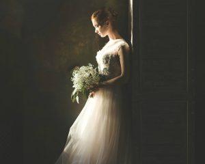donkere foto van een bruid met bruidsjurk en boeket royals