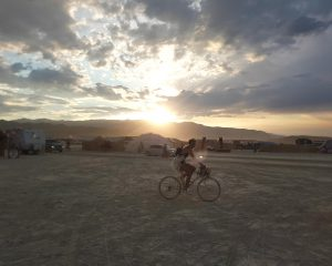 Iemand fietst langs op de Playa op Burning Man.