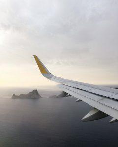 vliegtuigvleugel boven de oceaan. After travel dip.