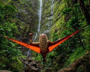 Vrouw in een soort hangmat voor een waterval. Solo reizen.
