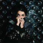 Model verstopt haar gezicht achter haar handen. Donkere foto. Chanel.